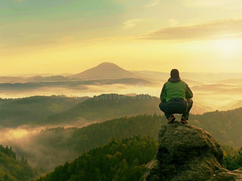 De wandelaarmens neemt een rust op bergpiek De mens zit op scherpe top en geniet van spectaculaire mening royalty-vrije stock afbeeldingen