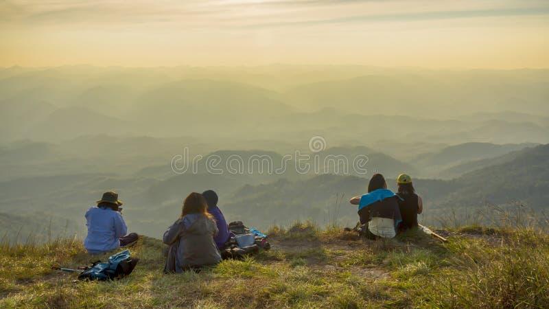 De wandelaarmensen nemen een rust en zitten op bergpiek met de herfstmo stock fotografie