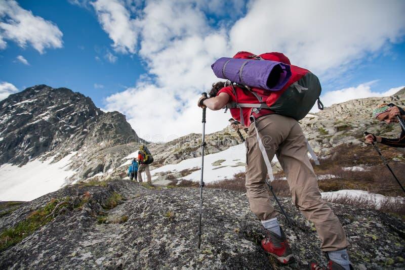 De wandelaars beklimmen rotsachtige helling van berg royalty-vrije stock afbeeldingen