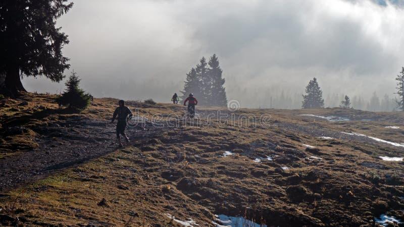 De wandelaars en de fietsers worden gesilhouetteerd op een bergsleep in het gebied van het Juragebergte van Zwitserland royalty-vrije stock foto's