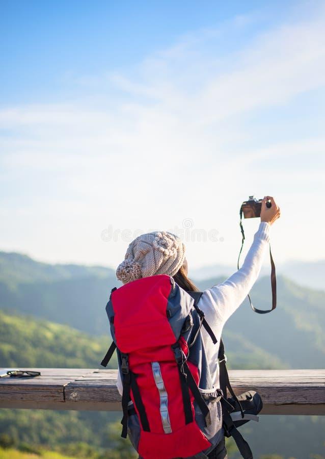 De wandelaarvrouw neemt een foto op de berg, blauwe hemel als achtergrond stock fotografie