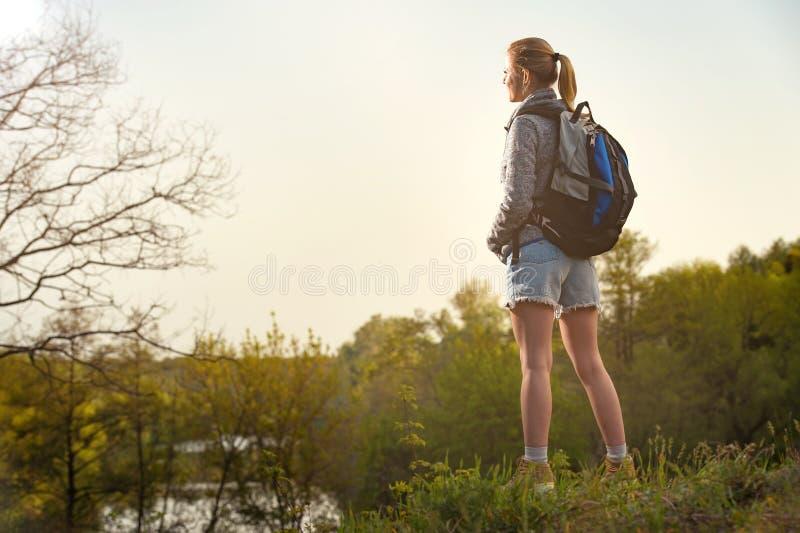 De wandelaarvrouw neemt een rust tijdens de zomersexpeditie Het meisje is blik stock afbeelding