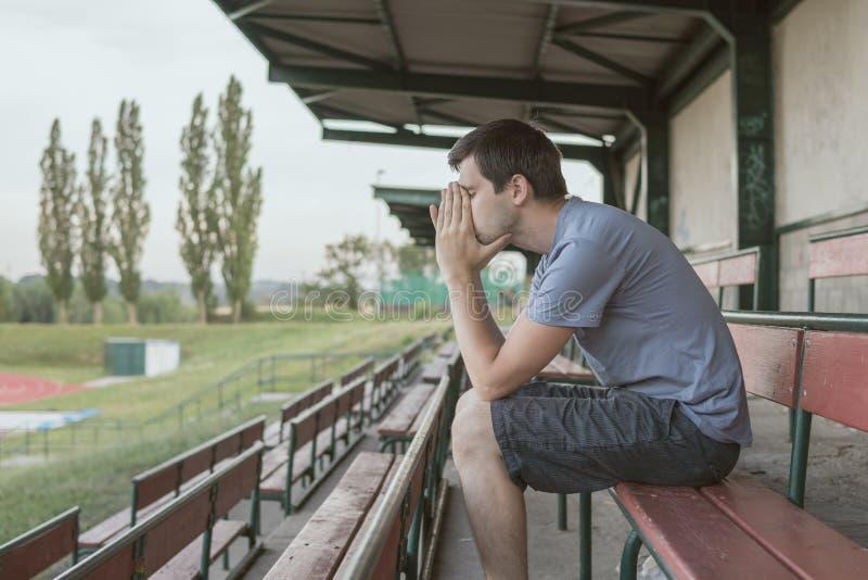 De wanhoop en de gedeprimeerde mens zitten op bank bij stadion stock afbeelding