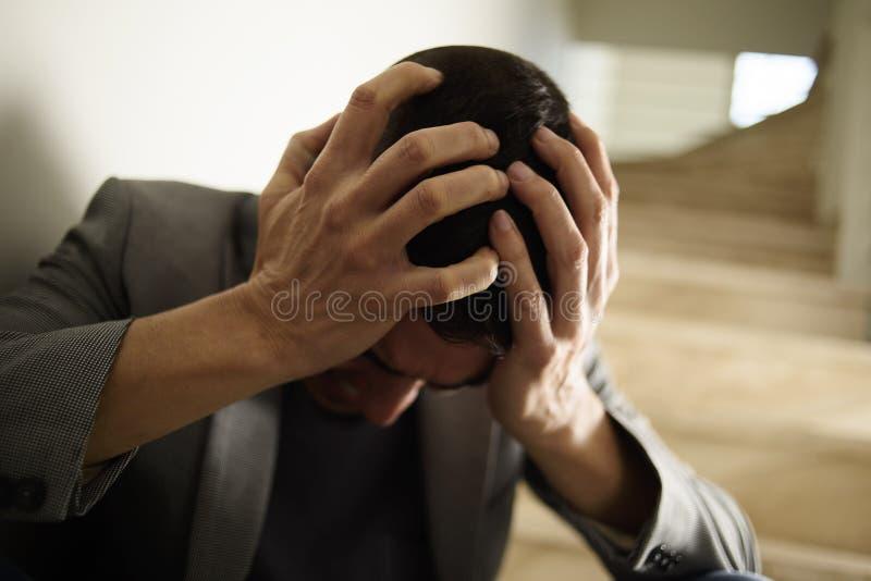 De wanhopige mens met van hem dient zijn hoofd in royalty-vrije stock foto's