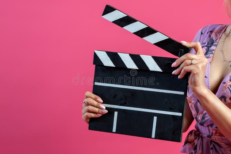 De wapens van meisje in purpere sundress houdt een open clapperboardfilmmaker in zwarte met witte strepen beginnen een film op a  royalty-vrije stock afbeeldingen