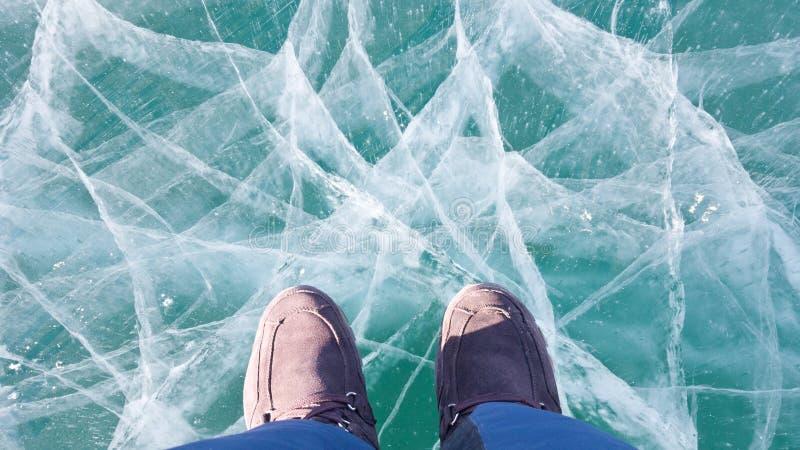 De warm opstarten van de suèdewinter op de voeten van de reiziger op het heldere blauwe ijs van meer Baikal Groot mooi barstnetwe stock fotografie
