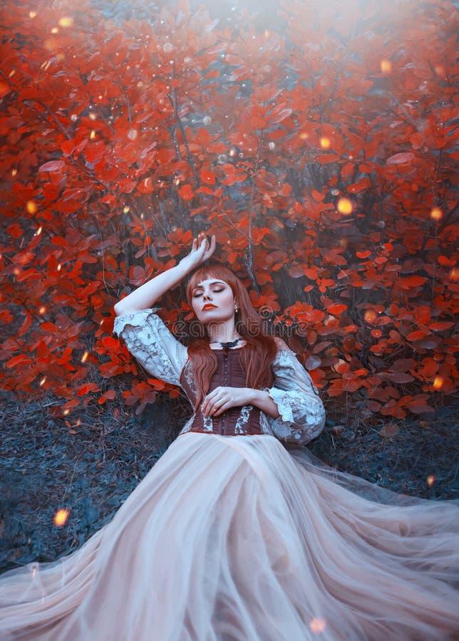 De warme kunstfoto van slaapschoonheid, meisje met vurig rood haar ligt op grond in dicht bos onder oranje bladeren in helder royalty-vrije stock foto