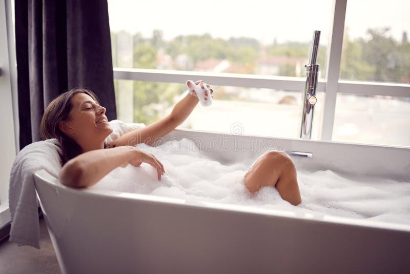De waslichaam van de vrouw jonge dame die bad thuis nemen stock afbeelding