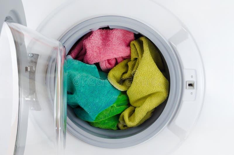 De wasmachine met kleurenhanddoeken, kleren, opent royalty-vrije stock afbeeldingen