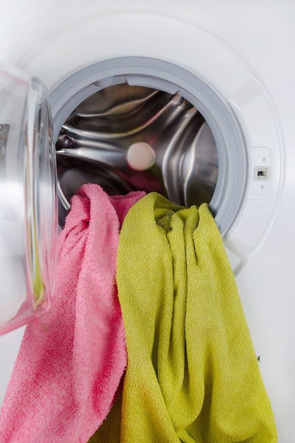 De wasmachine met kleurenhanddoeken, kleren, opent stock afbeeldingen