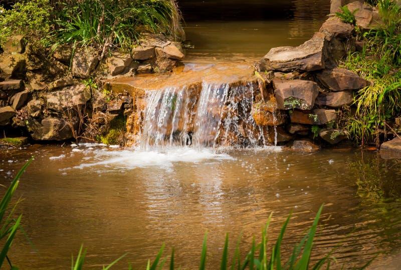 De watercascades over een mens gemaakt tot water vallen stock foto