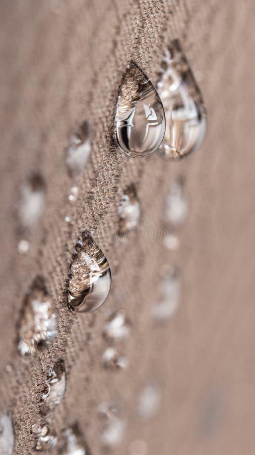 De waterdruppeltjes op vochtigheids bestand stof sluiten omhoog royalty-vrije stock foto's