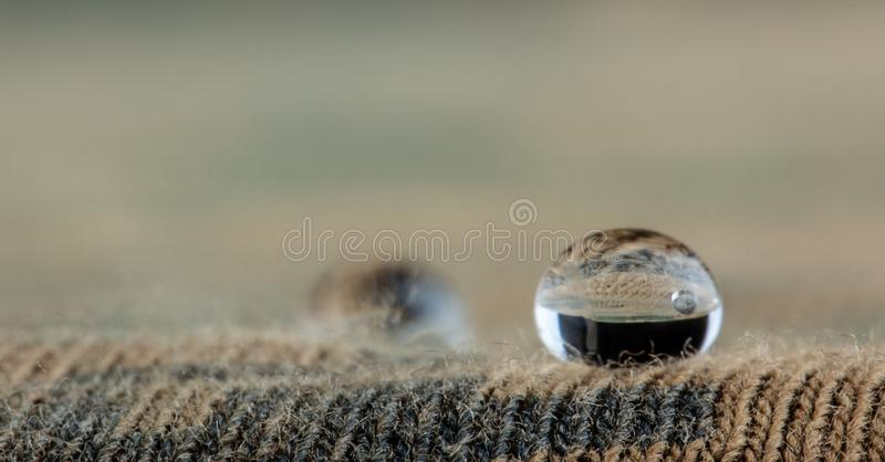 De waterdruppeltjes op vochtigheids bestand stof sluiten omhoog stock foto