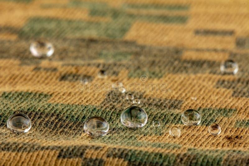 De waterdruppeltjes op vochtigheids bestand stof sluiten omhoog stock foto's