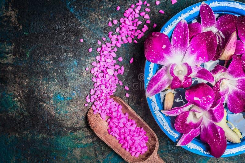 De waterkom met roze orchidee bloeit op donkere achtergrond met schop van overzeese zoute, hoogste mening stock afbeeldingen