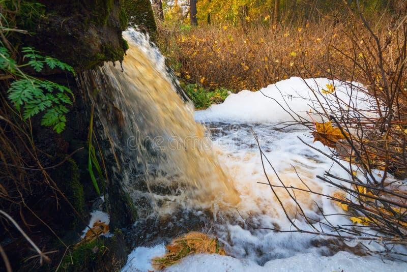 De waterval die uit de vijver in de herfst schuimen stock fotografie