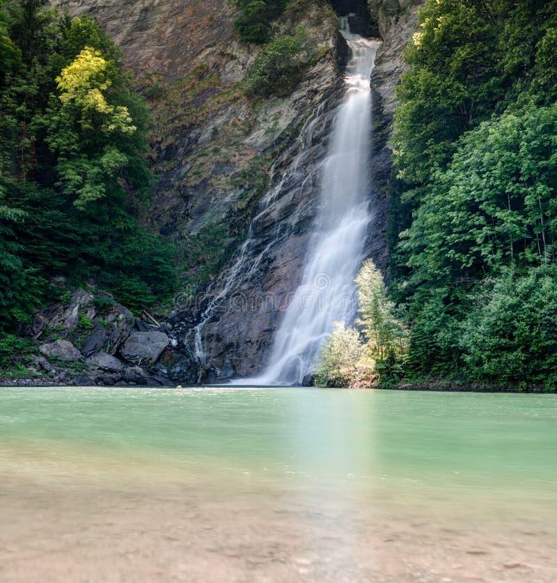 De waterval in midden van boslandschap die in clorful draperen turquopise en bruine vijver royalty-vrije stock foto's