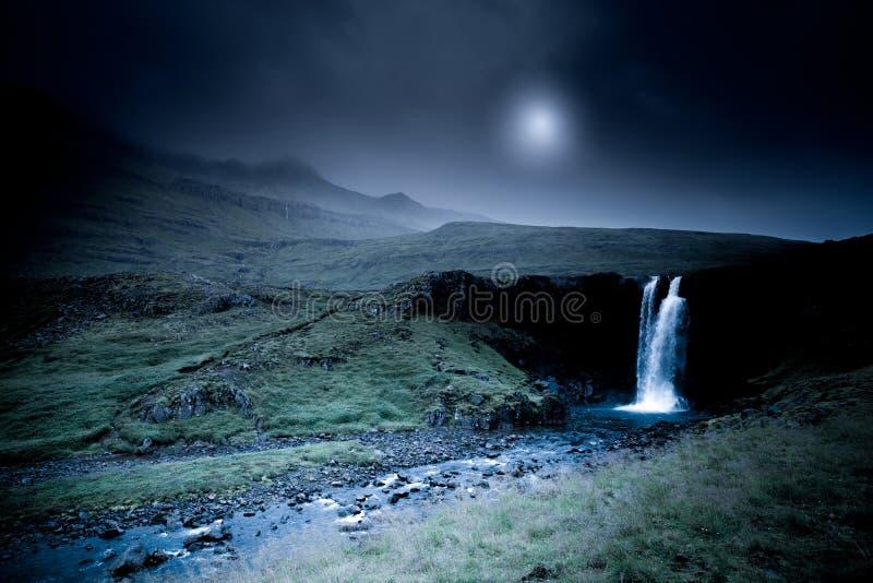 De waterval van IJsland bij nacht met maan stock foto