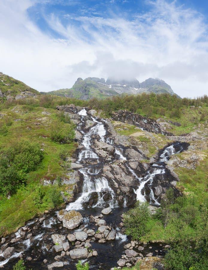 De waterval van Noorwegen Lofoten Moskenes met berg op de achtergrond Mooi de zomerpanorama stock fotografie