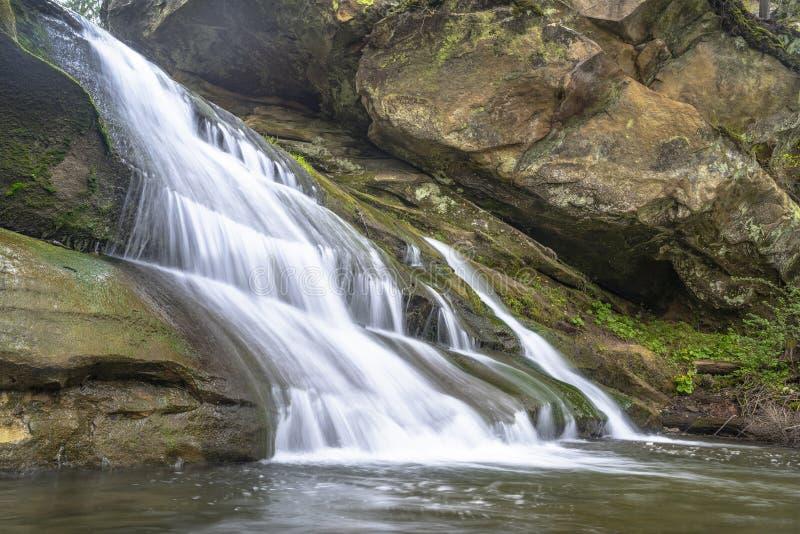 De watervallandschap van de bergrivier De stroom van de steencascade onder rotsen stock afbeelding