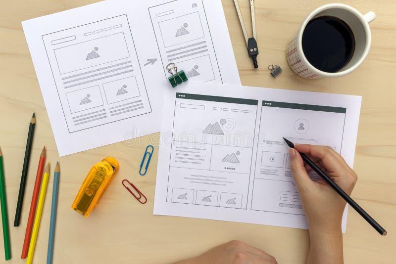 De website van de ontwerpertekening wireframes op houten bureau stock fotografie