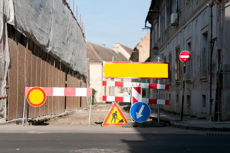 De wederopbouwplaats van de het werk vooruit straat met teken en omheining als wegbarricade stock foto