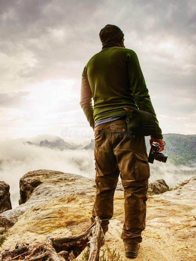 De weersomstandigheden van de fotograafcontrole Freelancer met camera op klip stock foto's