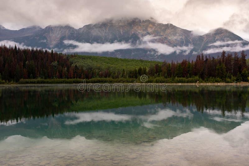 De weerspiegeling van het bos en de bergketen wanneer het kijken over Piramidemeer in Jasper National Park, Alberta, Canada, vroe stock afbeeldingen