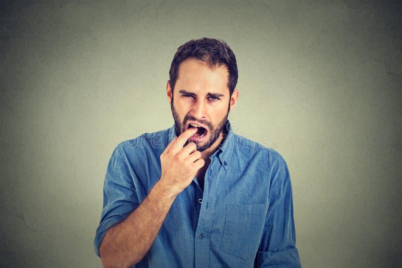 De weerzinwekkende mens met vinger in mond niet beviel met situatie klaar omhoog te werpen stock afbeeldingen