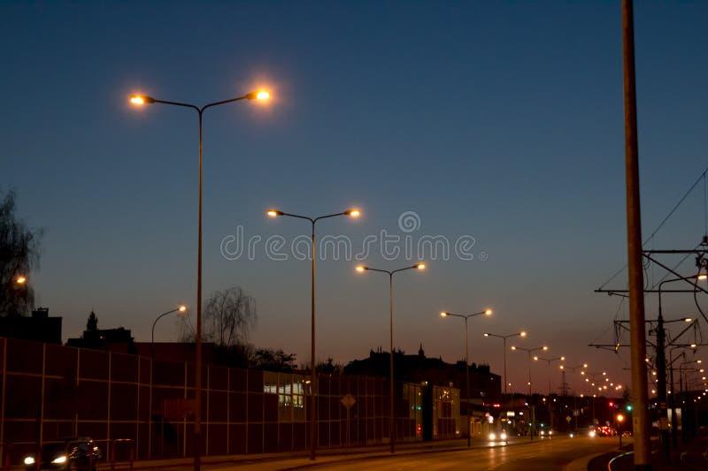 De weg in de avond met auto's en brandende ulicnilampen, tegen de achtergrond van schemer en de donkerblauwe hemel royalty-vrije stock afbeelding
