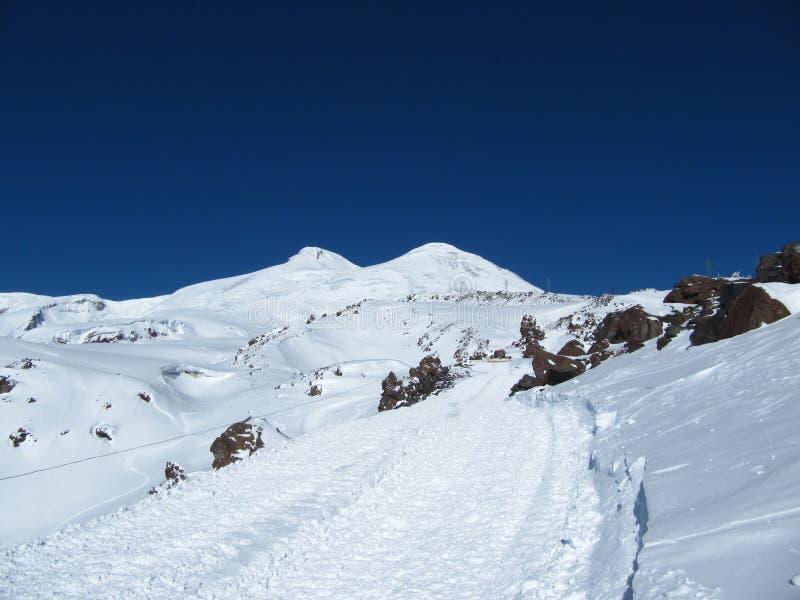 De weg die naar snowcat gaat en toeristen op de achtergrond van het dubbel-geleide onderstel Elbrus neemt royalty-vrije stock afbeelding