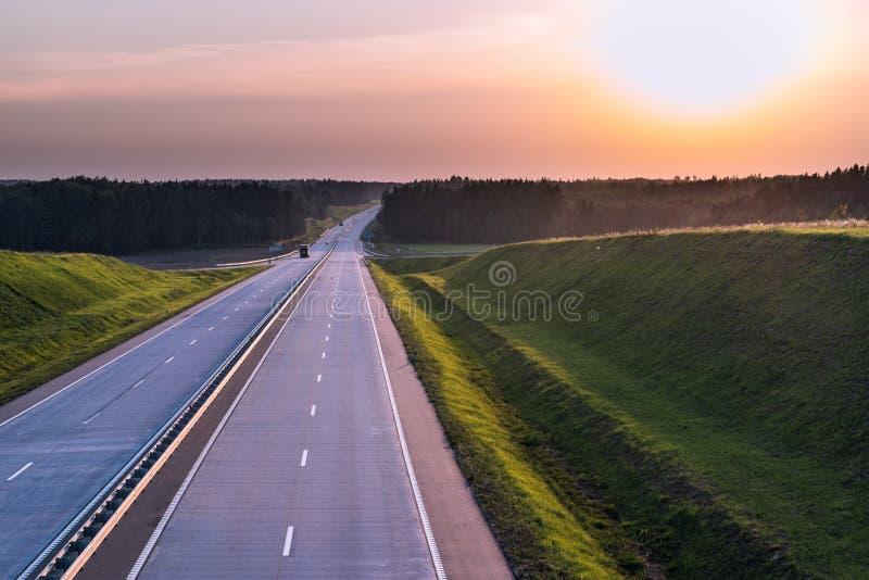 De Weg en de zonsondergang van het land Duidelijke weg grote aard rond stock foto's