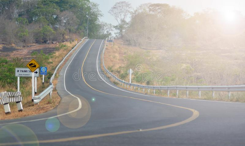 De weg heeft een gele lijn en er is een waarschuwingsbord neer op de steile linkerkant van hem stock fotografie