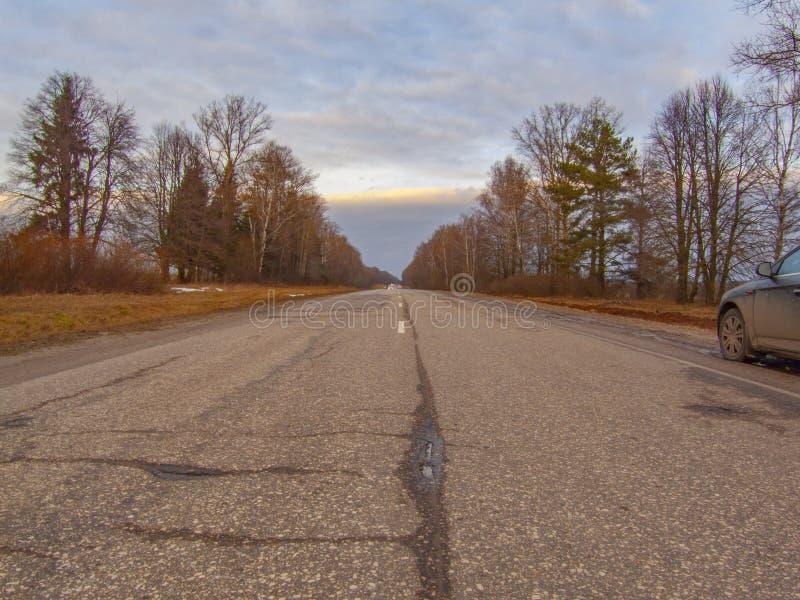 De weg in de herfst, in wat plaatsensneeuw is reeds zichtbaar royalty-vrije stock afbeeldingen