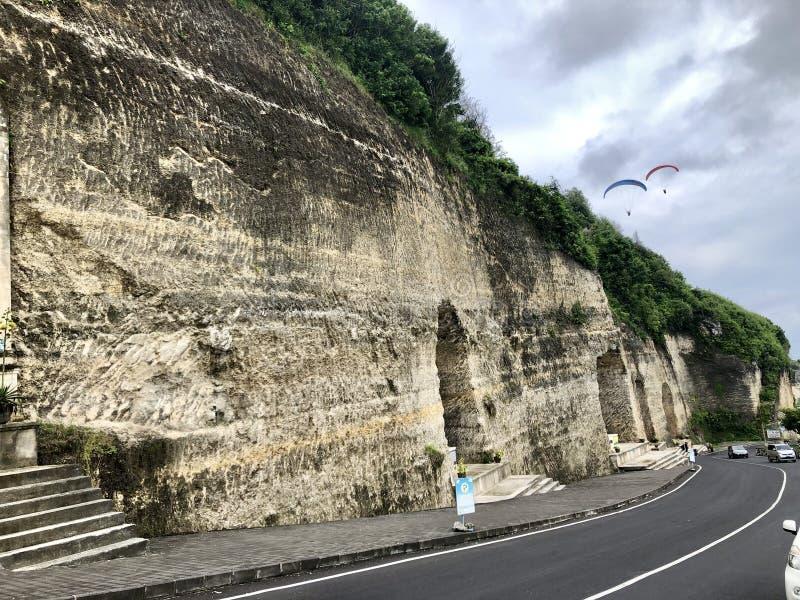 De weg in het midden van bos aan mening van overzees vanaf de bovenkant van heuvel wordt gezien die stock fotografie
