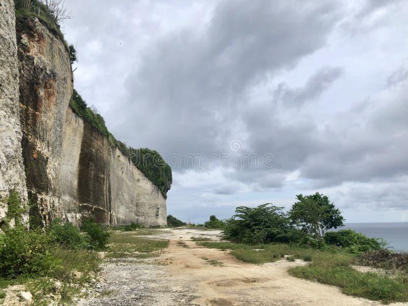 De weg in het midden van bos aan mening van overzees vanaf de bovenkant van heuvel wordt gezien die stock afbeelding