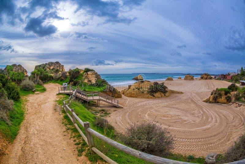 De weg onder de rotsen en de groene heuvels die tot het beroemde strand in Alvor, Algarve, Portugal leiden royalty-vrije stock foto's