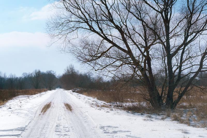 De weg is ongeplaveid onder sneeuw, snow-covered wegen buiten de stad stock foto's