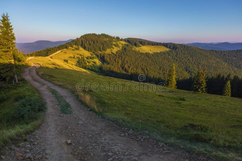 De weg op de bergrand op een zonnige dag stock fotografie