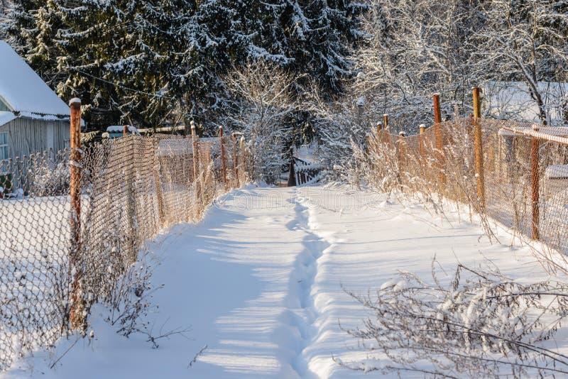 De weg in de sneeuw tussen twee binnenplaatsen royalty-vrije stock fotografie