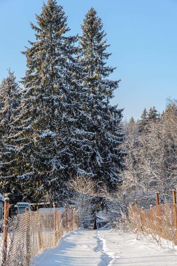 De weg in de sneeuw tussen twee binnenplaatsen stock afbeelding