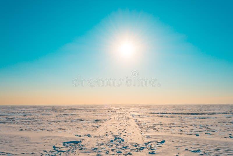 De weg in de sneeuw in de de winter sneeuwwoestijn in de turkooise hemel de heldere zon glanst stock afbeeldingen