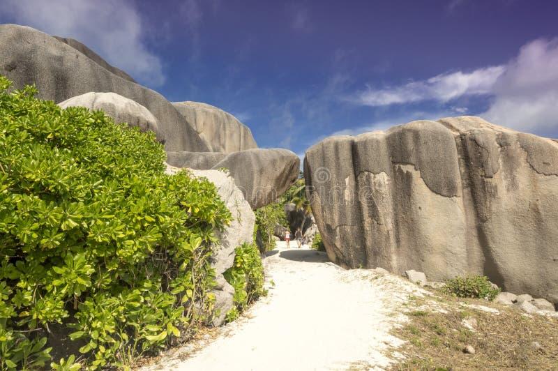 De weg tussen keien schommelt het eiland Seychellen, vakantieachtergrond van La Digue stock fotografie