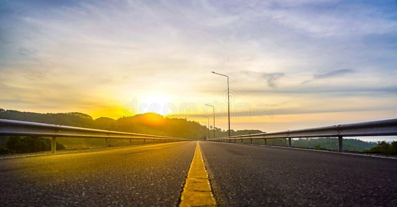 De weg van de berg Landschap met rotsen, zonnige hemel met wolken en mooie asfaltweg in de avond royalty-vrije stock fotografie