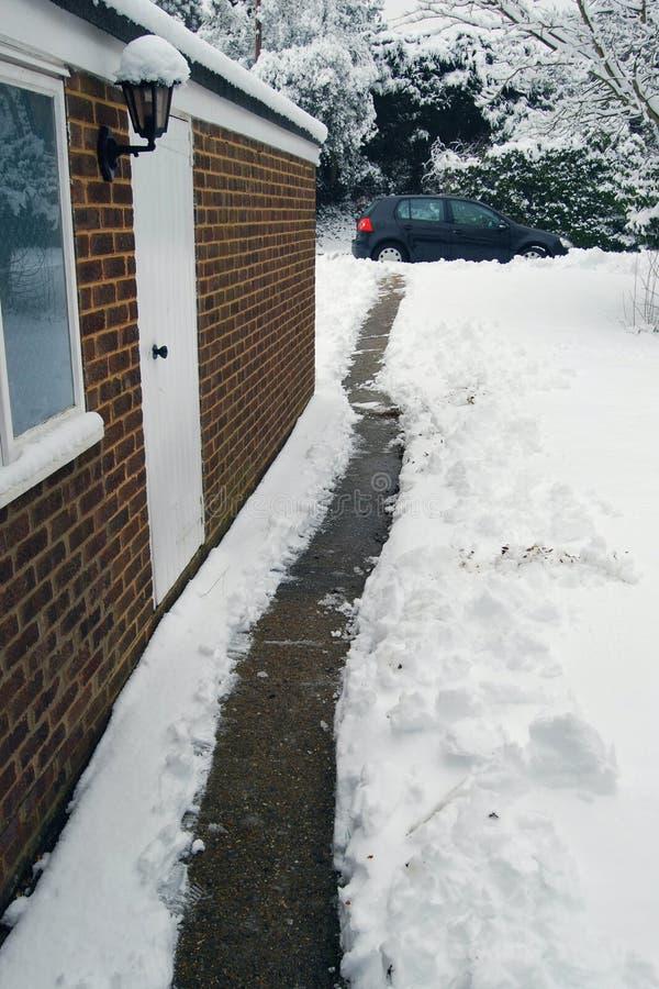De weg van de tuin die door sneeuw van huis aan auto wordt ontruimd stock afbeelding