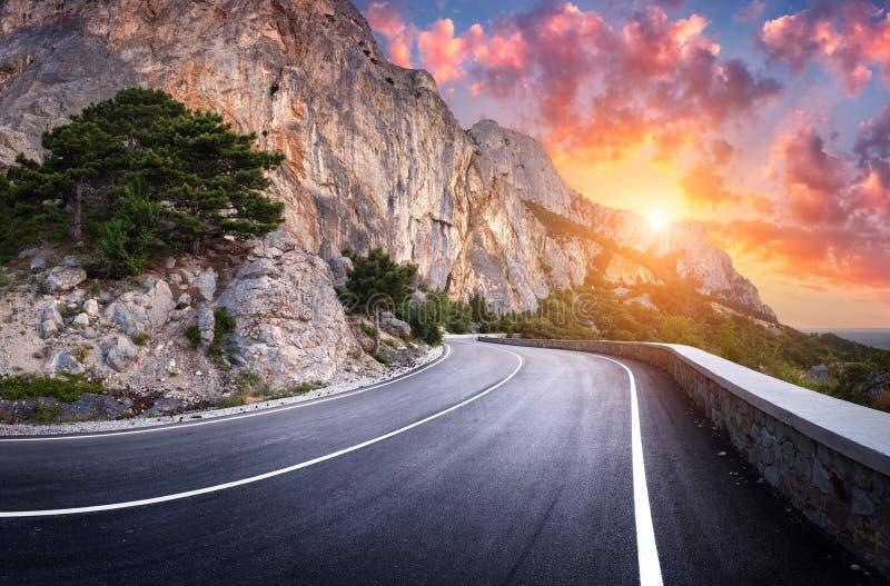 De weg van het asfalt Kleurrijk landschap met mooie windende berg royalty-vrije stock afbeeldingen