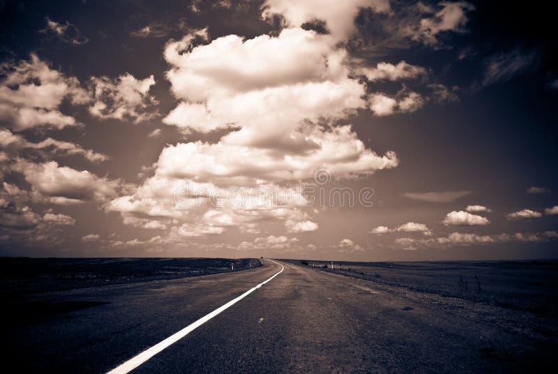 De weg van het platteland aan horizon royalty-vrije stock afbeelding