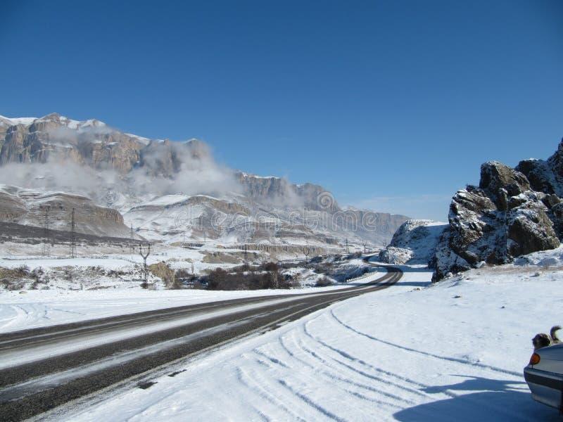 De weg van de de winterberg van de weghelling rotsachtige bergen in de wolken tegen een duidelijke blauwe hemel stock foto