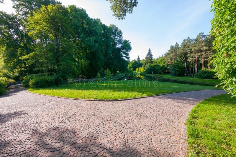 De weg wordt opgemaakt met een steenbestrating in een mooi groen park op een de zomer bewolkte dag Een goede plaats langs te onts stock afbeelding