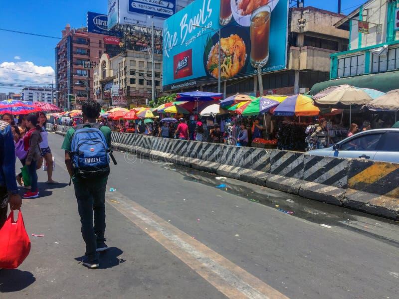 De wegkant van een nationale verkeershub in Metro Manila, overvol door mensen die verschillende objecten verkochten om een vlooie stock afbeelding